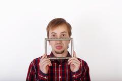 El hombre joven con la barba en camisa roja a cuadros muestra la lengua Fotos de archivo libres de regalías