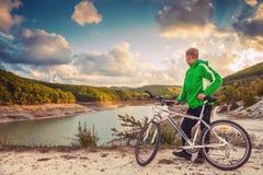 El hombre joven con la bici goza con la opinión hermosa del lago de la montaña Foto de archivo libre de regalías