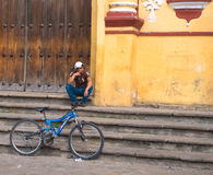 El hombre joven con la bici que descansa sobre iglesia camina Imagen de archivo