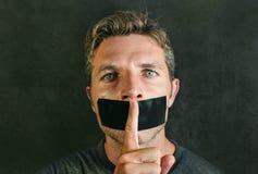 El hombre joven con la boca y los labios sellaron cubierto con la cinta adhesiva en la libertad de expresión forzada censura y si foto de archivo