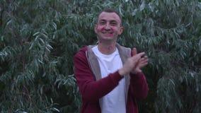 El hombre joven con la cara de las marcas de la barra de labios de besos está aplaudiendo por completo las manos almacen de metraje de vídeo