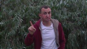 El hombre joven con la cara de las marcas de la barra de labios de besos está desaprobando por completo con la muestra de la mano almacen de metraje de vídeo