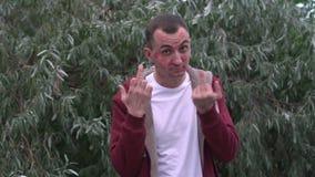 El hombre joven con la cara de las marcas de la barra de labios de besos está mostrando por completo el dedo medio almacen de metraje de vídeo