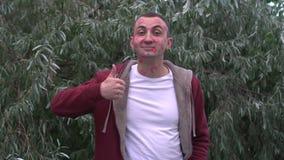 El hombre joven con la cara de las marcas de la barra de labios de besos está mostrando por completo el pulgar para arriba almacen de metraje de vídeo