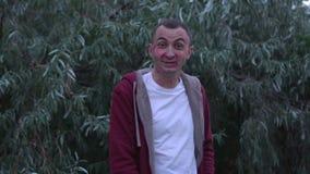El hombre joven con la cara de las marcas de la barra de labios de besos está riendo por completo, cara feliz almacen de metraje de vídeo