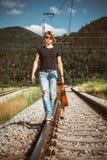El hombre joven con la guitarra camina en ferrocarriles Imagenes de archivo