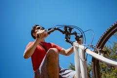 El hombre joven con las gafas de sol monta una bicicleta de debajo tiro imagen de archivo