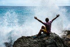 El hombre joven con las manos aumentadas que se sientan en la roca con el mar agita Imagen de archivo