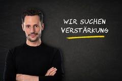El hombre joven con los brazos cruzados y 'Wir suchen texto del dich 'en un fondo de la pizarra Traducción: 'Le estamos bu ilustración del vector