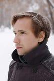 El hombre joven con los copos de nieve en pelo mira distancia Imágenes de archivo libres de regalías