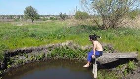 El hombre joven con los dreadlocks se sienta en la orilla del lago y disfruta de la naturaleza almacen de video