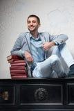 El hombre joven con los libros se sienta en un piano Foto de archivo libre de regalías