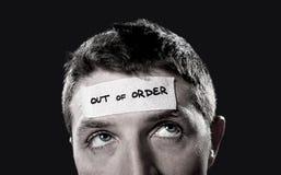 El hombre joven con los ojos azules y la cinta mandan un SMS a fuera de servicio en la frente en mente vacía seca Imagenes de archivo