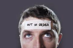 El hombre joven con los ojos azules y la cinta mandan un SMS a fuera de servicio en la frente en mente vacía seca Imagen de archivo libre de regalías