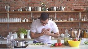 El hombre joven con los vidrios corta verduras en la cocina y experimenta una angustia aguda almacen de video