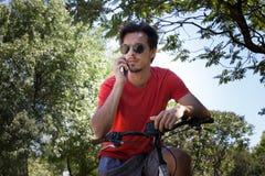 El hombre joven con smartphone del uso de las gafas de sol se sienta en la bici en parque imagenes de archivo