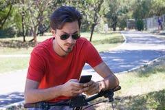 El hombre joven con smartphone del uso de las gafas de sol se sienta en la bici en parque foto de archivo libre de regalías