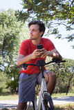 El hombre joven con smartphone del uso se sienta en la bici en parque fotos de archivo