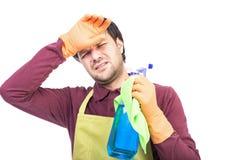 El hombre joven con sostenerse del delantal y de los guantes cansó para limpiar Imagen de archivo
