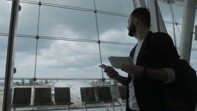 El hombre joven con el teléfono y el boleto se está colocando en el edificio del aeropuerto almacen de video