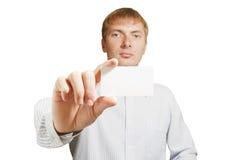 El hombre joven con un blanco firma adentro sus manos Fotografía de archivo libre de regalías