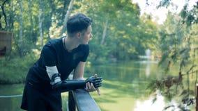 El hombre joven con un brazo biónico es puente cercano derecho del río almacen de metraje de vídeo