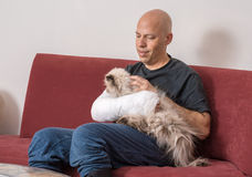 El hombre joven con un brazo echó acariciar su gato fotografía de archivo libre de regalías