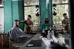 El hombre joven con una barba sienta en la silla en frente el espejo en una peluquería de caballeros El peluquero seca los pelos  imágenes de archivo libres de regalías