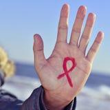 El hombre joven con una cinta roja para la lucha contra AYUDA en su ha Imagenes de archivo