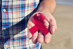 El hombre joven con una cinta roja para la lucha contra AYUDA, filtrado Foto de archivo libre de regalías