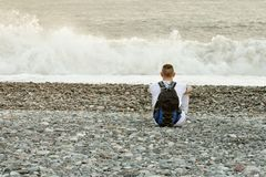 El hombre joven con una mochila se está sentando en la orilla del océano Visión desde la parte posterior Fotos de archivo