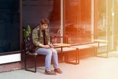 El hombre joven con una mochila y un cigarrillo utiliza un smartphone fotos de archivo