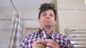 El hombre joven con una resaca por la mañana en el cuarto de baño sujeta su camisa y se pone en orden metrajes