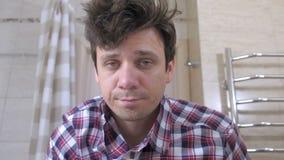El hombre joven con una resaca por la mañana en el cuarto de baño sujeta su camisa y se pone en orden almacen de metraje de vídeo