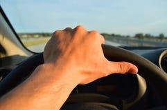 El hombre joven conduce su coche Foto de archivo