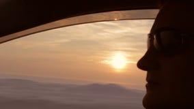 El hombre joven conduce un coche bajo puesta del sol lleva las gafas de sol Ciérrese encima de tiro del perfil almacen de video