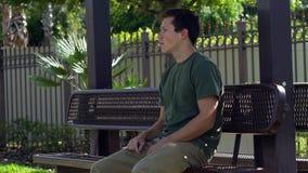 El hombre joven consigue la sentada frustrada en la parada de autobús, 4K almacen de metraje de vídeo