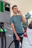 El hombre joven conversa en el teléfono mientras que reaprovisiona el coche de combustible foto de archivo