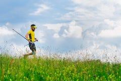 El hombre joven corre abajo en la hierba verde mientras que practica el nordic w Fotografía de archivo