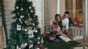 El hombre joven cubre con cuidado a su novia con la manta caliente Pares en el amor que celebra la Navidad metrajes