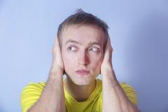 El hombre joven cubrió los oídos con sus manos No oiga Imagen de archivo libre de regalías