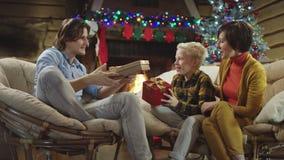 El hombre joven da regalos de Navidad a sus miembros de la familia metrajes