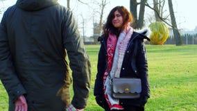 El hombre joven da a su novia un regalo y después la abraza, tiro 4k almacen de metraje de vídeo