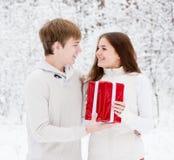 El hombre joven da un presente a su novia para la Navidad Fotografía de archivo
