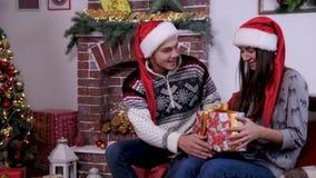 El hombre joven da un regalo de la Feliz Navidad para su novia almacen de video
