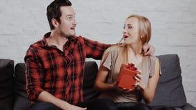 El hombre joven da un regalo a una muchacha en el sofá