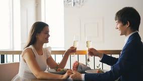 El hombre joven de amor está hablando con su prometido que sostiene el vidrio del champán después que tintinea los vidrios y que  almacen de metraje de vídeo