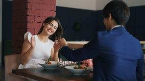 El hombre joven de amor está haciendo oferta a su novia en el restaurante, muchacha está diciendo sí, novio la está dando almacen de metraje de vídeo