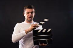 El hombre joven de aspecto caucásico está sosteniendo un clapperboard Por imagen de archivo libre de regalías