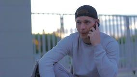 El hombre joven de la aptitud habla en el teléfono en la cámara lenta de la ciudad metrajes